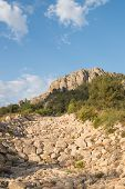 stock photo of ravines  - A dry ravine bed full of huge boulders - JPG