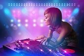 stock photo of disc jockey  - Pretty young disc jockey mixing music on turntables on stage with lights and stroboscopes - JPG