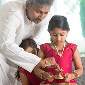 pic of deepavali  - Indian family in traditional dress preparing to celebrate diwali or deepavali at home - JPG