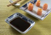 stock photo of soy sauce  - tasting salmon rolls with soy sauce - JPG