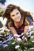 pic of girl next door  - Young beautiful girl next door with purple flowers in summer - JPG