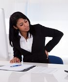 image of ordinary woman  - Young Businesswoman Sitting On Chair And Holding Her Back In Pain - JPG