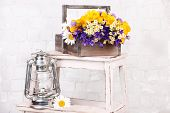 pic of kerosene lamp  - Beautiful flowers in crate with kerosene lamp on ladder on light background - JPG