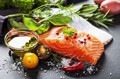stock photo of slating  - Delicious  portion of fresh salmon fillet  with aromatic herbs - JPG