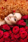 foto of perm  - Beauty Fashion Woman with long curly red hair and beautiful red roses bouquet - JPG