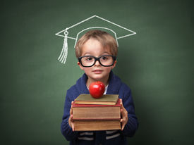 pic of child development  - Child holding stack of books with mortar board chalk drawing on blackboard concept for university education and future aspirations - JPG
