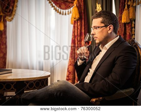 Middle-aged tasting cognac in luxury vintage style interior