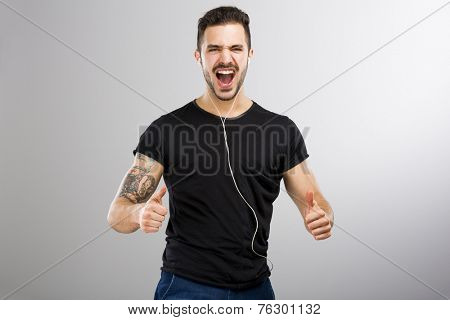 Beautiful and happy latin man listen music with thumbs up