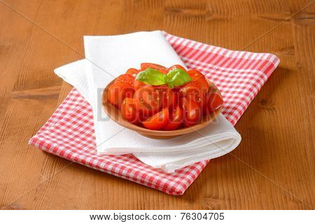 halved cherry  tomatoes with basil, served in the bowl with two kinds of fabric linen