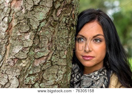 a young woman looks out from behind a tree