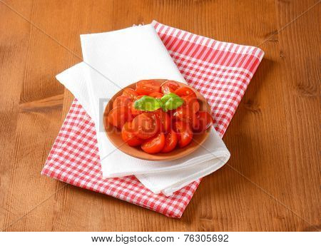 portion of halved cherry tomatoes with basil, served in the bowl with two kinds of fabric linen