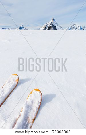 Ski tips, snow field and mountain landscape in background (the Matterhorn, Zermatt, Switzerland). Large white copy space.