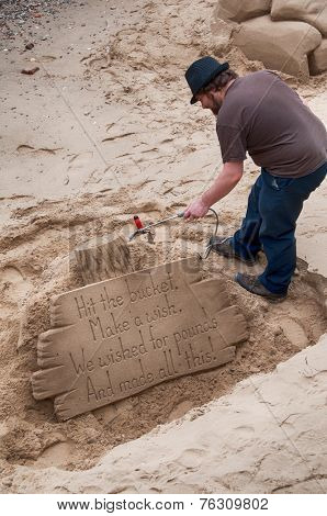 LONDON - 09 JUNE 2013: Artist working on a sand sculpture with a motivational message on a set of wooden planks on the south bank of the River Thames, London on 09 June 2013