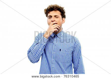 Portrait of a young man yawning over white background