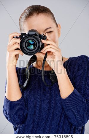 Female photographer taking a photo focusing the camera at the viewer as she composes her shot  over grey