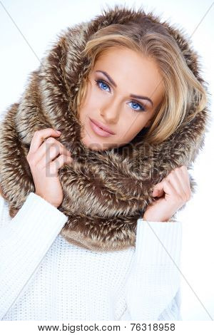Gorgeous blue eyed woman in winter fashion wearing a furry neck warmer pulled up onto her blond hair