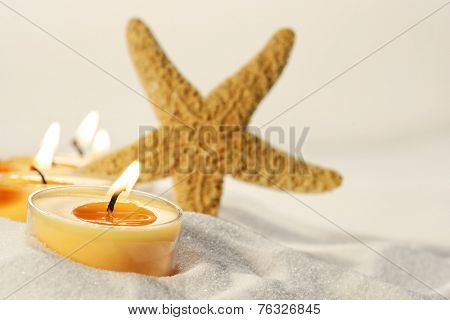 Orange tea light candles in sand with star fish