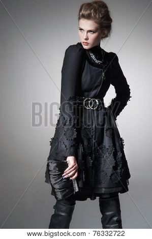 high Young fashion girl wearing elegant black clothes on gray background