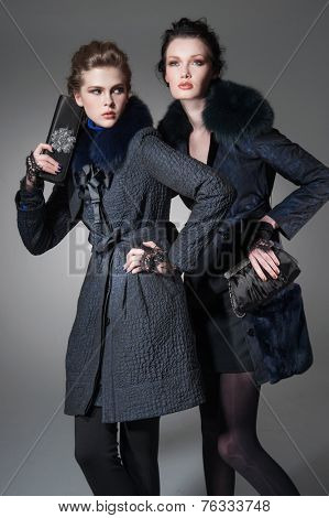 high young attractive two girl wearing fur coat holding purse on gray background