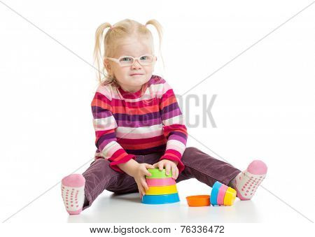 Funny child in eyeglases playing colorful pyramid toy isolated on white