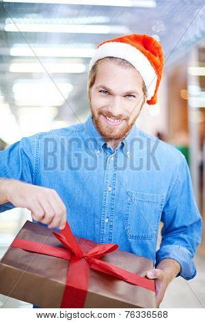 Young smiling man in Santa cap looking at camera while unpacking Christmas present