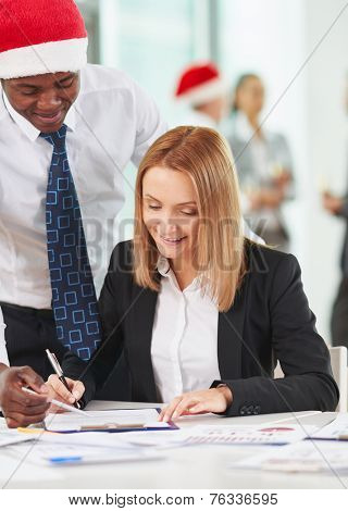 Pretty secretary going to sign document with African-american co-worker near by on background of their business partners