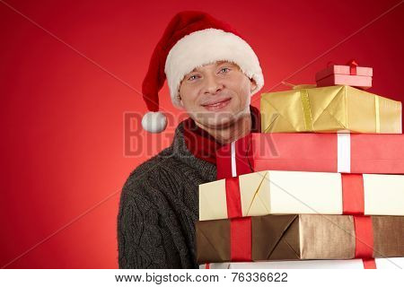 Santa man with pile of giftboxes looking at camera in isolation