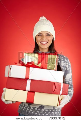 Portrait of lovely girl in winterwear holding heap of packages with gifts