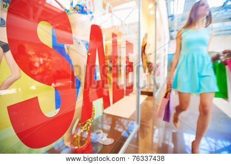 Word �¢??sale�¢?? on shop window and female shopper with paperbags walking on background