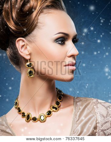 Close-up portrait of young and beautiful lady in a precious necklace and earrings