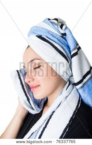beautiful young woman cleaning her face with a towel