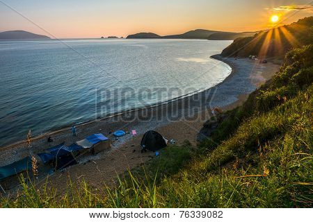 camping on the beach against sunset of russian isle Putyatin