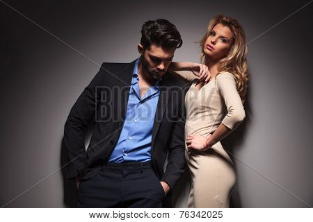 Attractive young business man looking down with his hands in pocket while his girlfriend is leaning on him, looking at the camera.