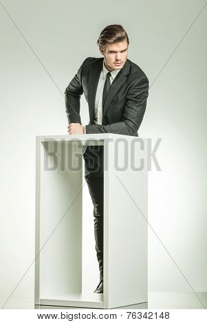 Young elegant business man looking at the camera while resting his arm on a white modern table.