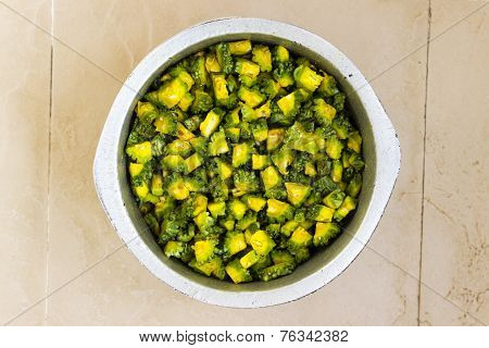 closeup of finely chopped bitter gourd kept in a vessel mixed with turmeric & chilli powder