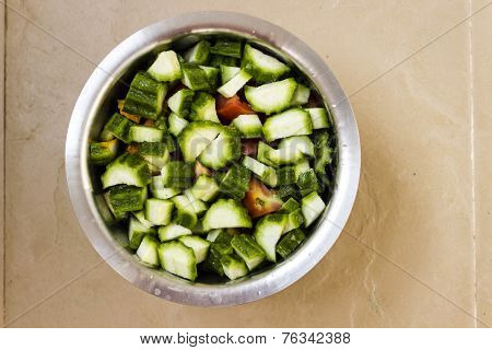 Finely chopped ridge gourd and tomatos kept in a vessel awaiting to be cooked