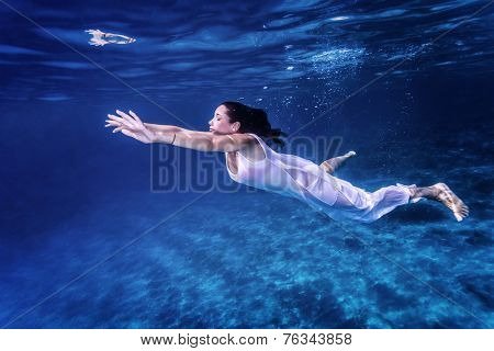 Beautiful female swimming underwater, wearing long white dress, fashion life, active lifestyle, summer vacation concept