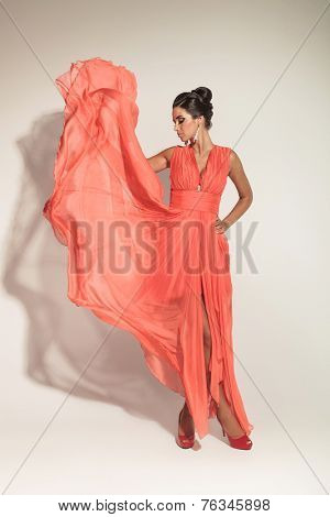 Elegant fashion woman looking down while fluttering her coral dress.