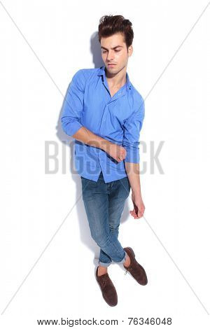 Handsome young fashion man pulling his sleeve while looking down, full body image.
