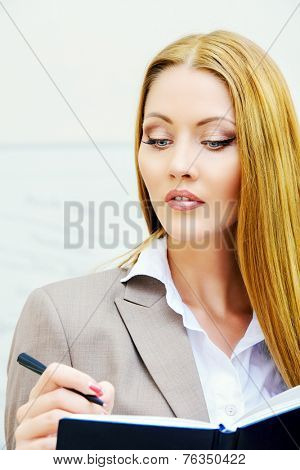 Portrait of a business woman making notes to her diary. Office, working process.