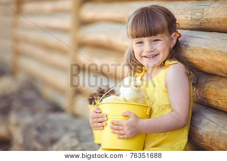 Happy little girl playing with chickens outdoors in the countryside