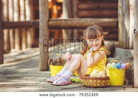 Happy little girl playing with the chickens outdoors in the countryside