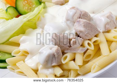 Chicken pieces on penne pasta topped with white bechamel sauce and served with a salad
