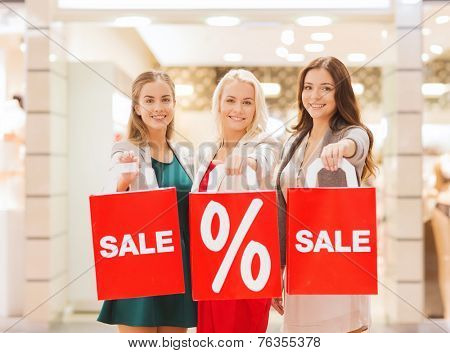 consumerism and people concept - happy young women holding shopping bags with sale and percentage sign in mall