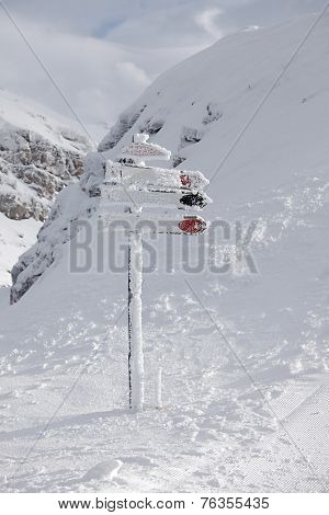 Directional sign post frozen in winter
