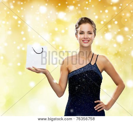 people  advertisement, christmas holydays and sale concept - smiling woman with white blank shopping bag over yellow lights and snow background