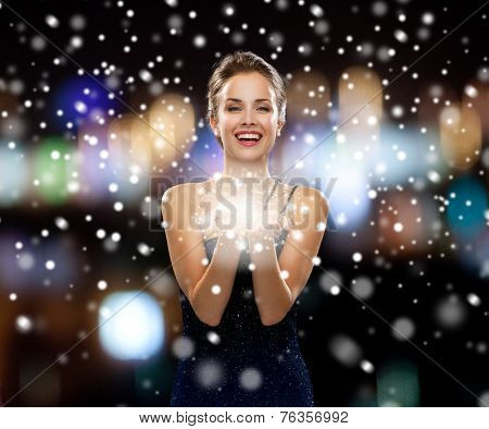 people, holidays, advertisement, christmas and luxury concept - laughing woman in evening dress holding something imaginary over night lights and snow background