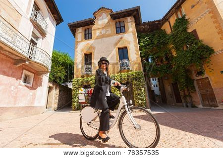 Girl with black elegant dress on a bicycle in the village square
