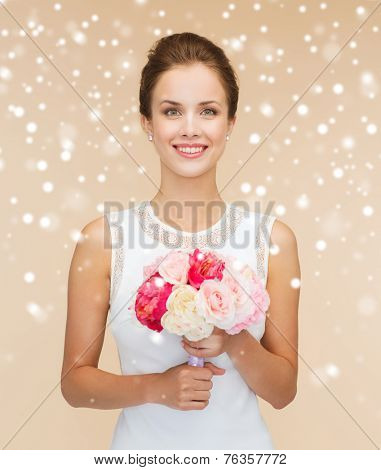 happiness, wedding, holidays and celebration concept - smiling bride or bridesmaid in white dress with bouquet of flowers over beige background and snow