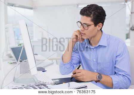 Casual graphic designer working at his desk in creative office